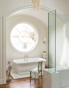 Magnificent huge round window over freestanding tub in luxurious white bathroom with arch and barrel ceiling, wood floors, and glass shower walls. Cliffwood project - Giannetti Home