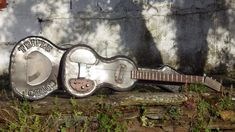 """This 3 string and accompanying case were made out of sheet metal from the outside of an old dishwasher. Tuners are cased in a little Dutch """"Panter"""" metal cigar box. The sides of the guitar were """"upholstered"""" with strips of old leather pants. The neck was made out of an old window frame, the fretboard still has the influences of the weather on it. It's tuned in GGB... Cigar Box Guitar, Sheet Metal, Making Out, Dishwasher, Cowboy Hats, Dutch, Leather Pants, Window, Weather"""