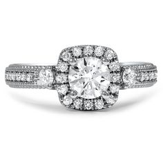 This engagement ring features a gorgeous round brilliant diamond surrounded by a luminous halo of diamond accents. A surprise diamond accent adorns both sides of the gallery with exquisite filligree and milgrain detailing for a truly vintage-inspired look.