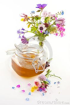 A closeup of honey in a preserving jar and a mixture of flowers