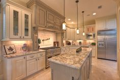 Great kitchen with white/cream cabinets, black hardware, grey blue island & granite cabinets.