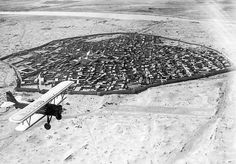 An airplane flies over Baghdad, Iraq, early 20th Century