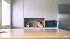 Puinen kahvi- ja teesyvennys keittiökaapeissa rikkoo harmaan pinnan.