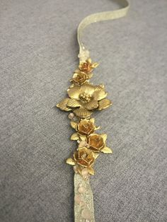 """Gold metal floral sash hand beaded with matte and sparkly glass beads. -3/8"""" x 6' metallic satin ribbon -Floral feature 1 5/8"""" at widest x 4.5"""" length -Glass beads Made in NY// Please allow 1-3 weeks for production if not in stock. Return/exchange within 10 days of r"""