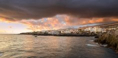 derliebewolf posted a photo:  A stormy sunset over the small village of Alcalà, Tenerife. This was during our first (out of four) weeks in Tenerife an each morning we were greeted by this view to the west where the Teno mountain range an the Los Gigantes Cliffs can be seen near the horizon. To the right (not visible due to the low hanging clouds) lies the Pico del Teide, Spains highest mountain. What a picturesque place to be!  Panaroma of two photos slightly cropped top and bottom. Nikon…