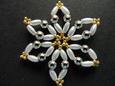 Vánoční hvězdička - 4 cm -perleťová zlatostříbrná Vánoční hvězdička v barvě zlatostříbrné barvě v kombinaci s bílými oválnými korálky. Hvězdička má průměr 4 cm a je vyrobena z lehoučkých plastových korálků s perleťovým a kovovým vzhledem. Hvězdička je lehoučká, krásně se bude vyjímat na vánočním stromečku, jako dekorace na stůl či jako ozdoba ...