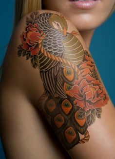 Colorful peacock with red flowers tattoo on shoulder