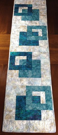 Modern Batik Table Runner, Teal & Taupe Quilted Tablerunner, Handmade Wallhanging, Reversible Table Quilt, Contemporary Dining Decor ----------------------------------------- Although designed as a modern look table runner, this quilt could also be used to adorn your wall, a dresser, coffee table, sofa table, buffet, desk, bed or piano top. The teal and taupe color scheme is versatile and can be used in any season. A layer of batting enclosed between two layers of cotton fabrics gives ex...