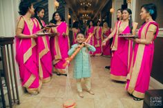 Bengali bridesmaids hold fruits and sweets to hand out to guests as they walk in to the mehendi / holud party
