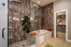 """In the en suite of the eclectic master bedroom, designers chose a wall tile that added texture in the space. The brown tile on the walls in the shower and bath tub spaces has a sort of """"underwater"""" feel, creating a softer space and a focal point for the bathroom. In the shower, brown and tan stained glass tile complement the bold wall choice, while a lime green patterned rug ties this master bathroom space into the master bedroom."""