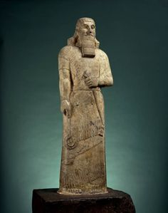 Carved magnesite statue of Ashurnasirpal II on reddish dolomite stand. Reign of Ashurnasirpal II. Neo-Assyrian. 883 - 859 B.C. | The British Museum
