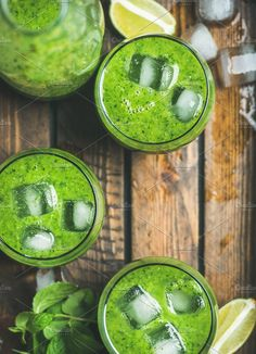 #Fresh green smoothie with ice cubes  Fresh green smoothie in bottle and glasses with ice cubes mint and lime in wooden tray top view selective focus copy space. Clean eating detox vegetarian weight loss raw healthy food concept