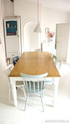 Une salle à manger au style scandinave et aux chaises dépareillées.