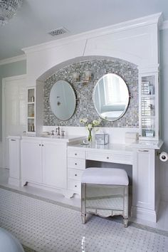 A backsplash of lustrous glass tiles beneath an arched opening elevates the vanity wall of this master bath to focal-point status. The vanity incorporates a makeup area at sit-down height, as well as twin mirrors and glass-front display cabinets Bad Inspiration, Bathroom Inspiration, Bathroom Built Ins, Bathroom Renos, White Bathroom, Bathroom Cabinets, Bathroom Ideas, Bathroom Pics, Vanity Bathroom