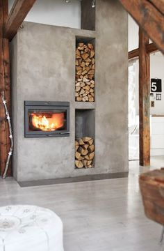 Industriële haard in een strakke woonkamer met handige opbergvakken voor het hout | Industrial fireplace with useful compartments for wood
