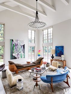 The living room of powerhouse gallery owner Dominique Lévy and movie producer Dorothy Berwin's Hamptons home, features artworks by, from left, Anselm Reyle, Ugo Rondinone, and Zhu Jinshi | archdigest.com