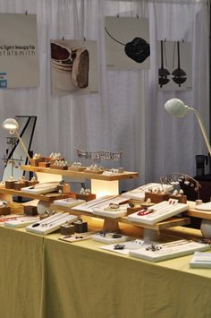 Natural wood shelving rests on mod rectangular lamps. She also uses small vases turned upside down under the front shelving. The jewelry is display on fabric wrapped canvases. Colors are calm & soothing; Craft Fair Displays, Market Displays, Booth Displays, Stall Display, Display Ideas, Booth Ideas, Jewelry Booth, Jewelry Show, Craft Stalls