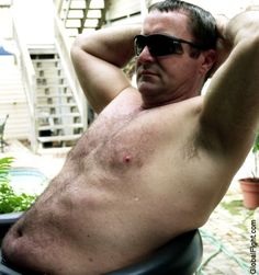 a handsome man lounging poolside suntanning bathing soaking daddy