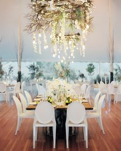 """American, Italian, Irish, and Swedish flags fluttered brightly above the white reception tent from Newport Tent Company at this soirée in Rhode Island. """"It was a fun way to bring it back to who we are and where we come from,"""" says the bride. Beneath the canopy was a modern assortment of tables and chairs, with the head table highlighted by an arrangement of wooden branches, orchids, and lights that twinkled from above."""