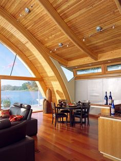 The curved ceiling of the Fennell House is made of Douglas fir and the floors are Brazilian cherry. The floating home's windows face west affording the open living space sunset views over the Willamette River.