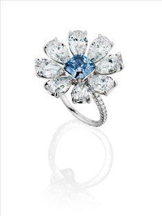 LEVIEV Fancy Vivid Blue Internally Flawless diamond mounted with eight pear-shaped D Internally Flawless diamonds totaling 11.85 carats, handcrafted in platinum
