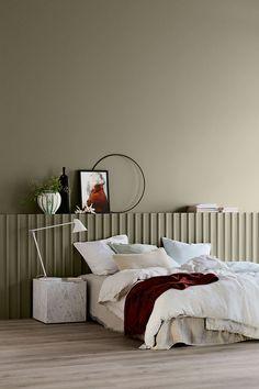 Simple bedroom design with beige walls, grey floor and white bedside lamp