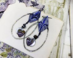 Materials:  Purple metal diamond connectors Embellished heart charms Glass beads Vintage mother of pearl buttons Vintage iridescent glass tube