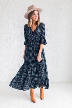 DETAILS: - V-neck dress with ruffle bottom - Navy color with pattern detail - Midi length - Model is wearing a small