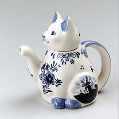 Delft Blue And White Cat Shaped Teapot With Raised Paw As Spout And Handle In Its Back Decorated In Traditional Delft Motifs Including A Windmill Ceramic