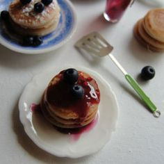 Mini Pancakes  The Artist: Kim Saulter, It's a miniature life  Can you believe those fluffy, lightly-browned pancakes and plump, sweet blueberries are actually made out of clay? Kim Saulter started making dollhouse miniatures more than 20 years ago after her first daughter was born. Three years ago she jumped into the world of food miniatures, and she hasn't looked back since. On her blog you'll find recreations of cakes, cookies, pies, muffins, doughnuts, and other treats.