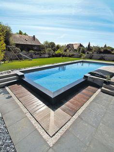 Le débordement par l'esprit piscine - 11 x 4 m Revêtement gris anthracite Escalier asymétrique Margelles et mur de débordement en granit Plage en granit et en ipé