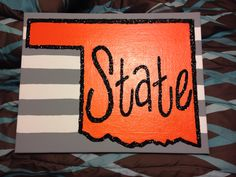 Oklahoma State canvas. White and gray striped background, orange and black outlined state, lettering in black, with all the black covered in glitter!