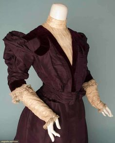 PLUM SILK DAY DRESS, c. 1899 2-piece faille, velvet band trim, net w/ lace trimmed under-sleeves & front plastron, trumpet shaped skirt.