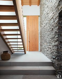 Oakley stone covers the walls of the entrance hall. Stair of Douglas Fir; handwoven basket from Ghana.