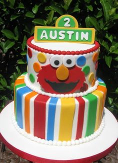 Cute Sesame Street Cake- cake with stripes, then Elmo and cookie monster toys on top with a 2