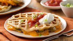 Fork into a melty cheddar center in these savory waffles. Toppers of salsa, sour cream and onion make a fiesta of flavors.