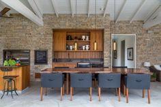 O terraço gourmet, coberto de pedra-madeira, é o xodó do marido. A mesa com tampo de tronco de noz comprado em Nova York acomoda até 12 convidados. Cadeiras estofadas da Casual Móveis.