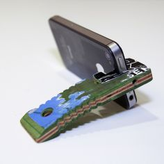 STVND - The worlds first iPhone accessory made from up-cycled skateboards. Keeps your headphones tangle free and props your phone up for hands free viewing.