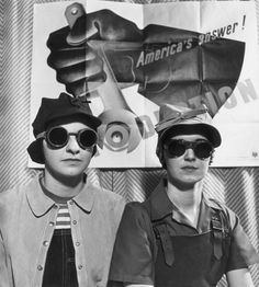 circa 1942: US propaganda image of two female factory workers, wearing wearing goggles, caps, and aprons, posing in front of a poster for the American homefront war effort during World War II (1939-1945), United States. (Photo by Hulton Archive/Getty Images)