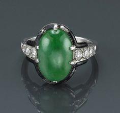 An art deco jadeite jade, diamond and enamel ring, Cartier, circa 1925 centering an oval-shaped jadeite jade; signed Cartier