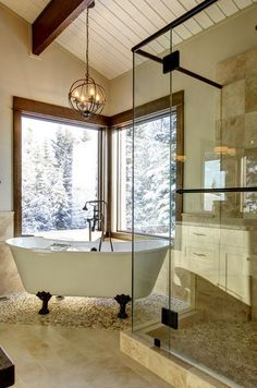 Rustic, classic, elegant. Clawfoot tub, river rock floors, wood ceiling beams, and a chandelier. Houzz.com