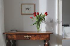 Frische Tulpen auf antiker Konsole / Minimalistic 19th century apartment with vintage details: fresh flowers on an antique console