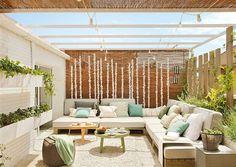 Porche exterior con sofas en L y suelo de piedras