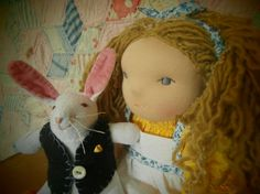 Alice is a classic body Waldorf doll made of organic cotton knit stuffed with wool, and lightly scented with lavender. She has embroidered blue eyes and hand dyed mixed yarn hair of various weights and hues, in wool and mohair. She is wearing a cotton print dress, apron trimmed with vintage eyelet, hand dyed tights, and a matching head bow. Shoes of wool felt with snaps. The white rabbit is made of cotton velour stuffed with wool, embroidered face, whiskers, embroidered wool felt waistcoat…