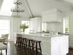 Dark wood stools make beautiful statement pieces in an all-white, open #kitchen.