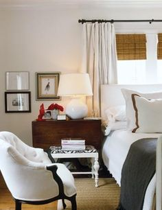 love this room // grey + white // traditional night stand w/stool; low gallery; rattan shades w/drapes; plain white headboard; hotel bedding; sisal rug; white tufted arm chair