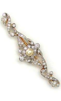 An Edwardian Diamond and Pearl Brooch, circa 1910. Platinum over 14K gold, the openwork scrolls set with Old European and single cut diamonds, with central pearl.