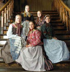 I trappen på Stavanger Museum sitter de samme jentene pluss en 5te, her har 4 av jentene fått på seg trøyer utenpå vesten. Trøyene kan sys enten som uteplagg eller som inneplagg. Den røde og den brunblomstrete er i trykt bomullsstoff, den blågrønne er brosjert ulldamask og den svarte er i ullmoare. Alle draktene har silketørkler som er i vanlig handel.