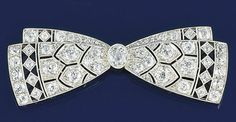 A diamond bow brooch  Of pierced twin bow design set with a central oval old brilliant-cut diamond in millegrain mount and old brilliant and rose-cut diamonds. Art Deco or Art Deco style.