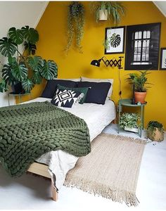 a mustard accent wall and touches of dark green and potted plants make up a bold boho space
